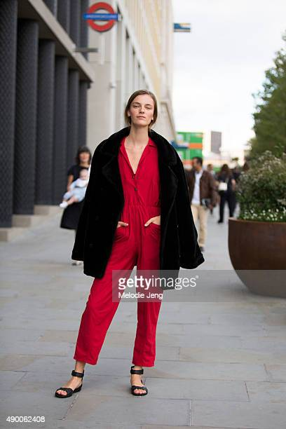 Model Laura Kampman wears a black jacket layered over a red jumpsuit and sandals during London Fashion Week Spring Summer 2016 at Kings Cross on...