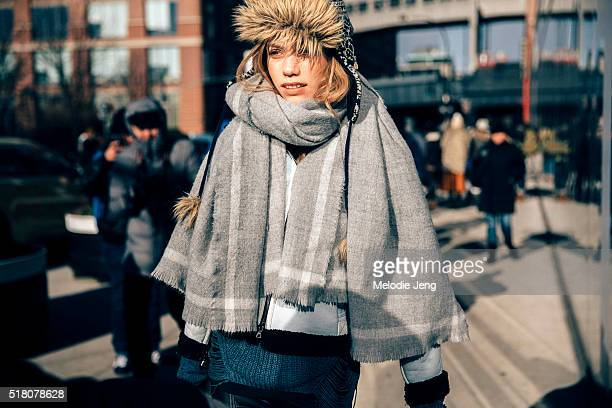 Model Laura Schellenberg exits the Tibi show at Skylight 60 Tenth in a fur cap and a wool/cashmere scarf with frayed edges during New York Fashion...