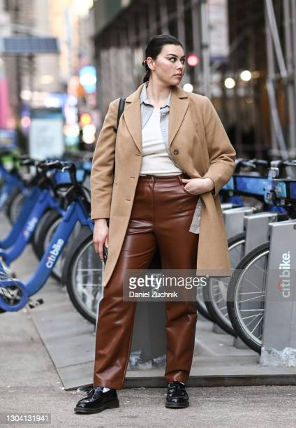 Model Lauren Chan is seen wearing a tan coat, white shirt, brown pants and black shoes outside the Christian Siriano show during New York Fashion...