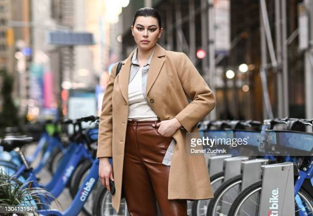 Model Lauren Chan is seen wearing a tan coat, white shirt, brown pants outside the Christian Siriano show during New York Fashion Week F/W21 on...
