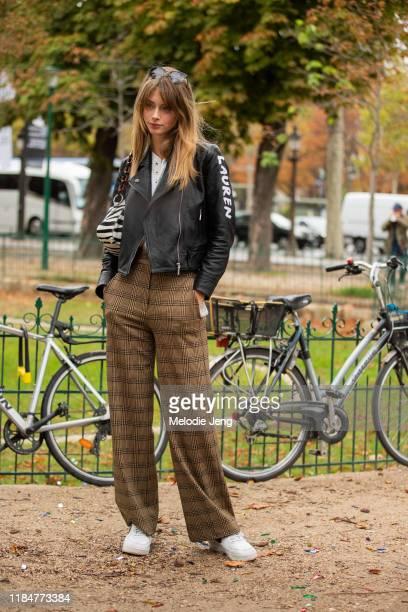 Model Lauren de Graaf wears a personalized Lauren black leather jacket zebra print bag brown houndstooth tattersall print pants and white Nike Air...