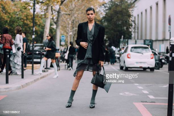 Model Lavinia de Paula wears a black blazer gray vest gray dress black purse gray socks and black heels during Paris Fashion Week Spring/Summer 2019...