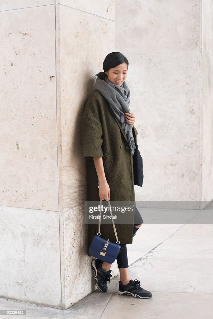 Model Leaf Zhang wears a Wu Yijian coat, Ash sneakers, ACNE scarf, Frima pants, and Valentino handbag on day 2 of Paris Haute Couture Fashion Week Spring/Summer 2015, on January 26, 2015 in Paris, France.