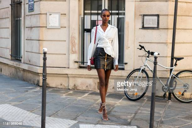 """Model Leila Nda wears red sunglasses, Messika Paris jewelry, a white asymmetrical top, a black Heron Preston """"handle with care"""" skirt, and wrap up..."""