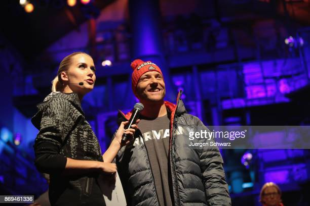 Model Lena Gercke tals to Moritz Mueller during the presentation of the outfit for German athletes competing in the upcoming Olympic Games in South...