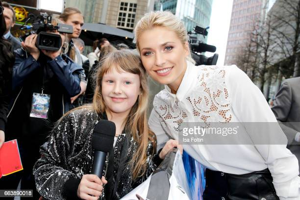 Model Lena Gercke with a kids reporter during the 'Die Schluempfe Das verlorene Dorf' premiere at Sony Centre on April 2 2017 in Berlin Germany