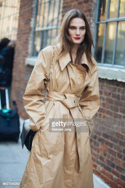 Model Lena Hardt wears a belted tan Lemaire trench on February 12, 2018 in New York City.