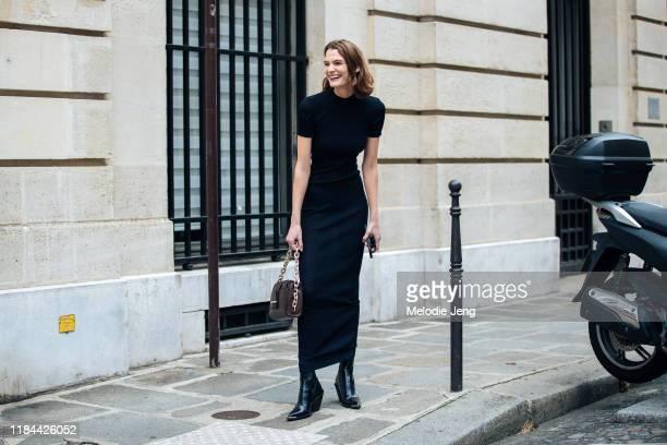 Model Lena Hardt wears a black form-fitting dress, brown bag, and black heeled boots after the Altuzarra show during Paris Fashion Week Spring/Summer...