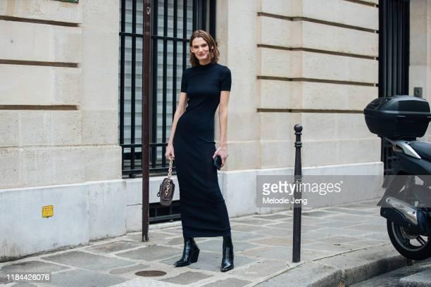 Model Lena Hardt wears a black formfitting dress brown bag and black heeled boots after the Altuzarra show during Paris Fashion Week Spring/Summer...