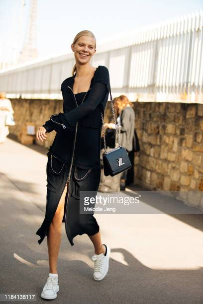 Model Lexi Boling wears a lack zip-up dress, black Louis Vuitton bag, and white Alexander McQueen sneakers after the Loewe show during Paris Fashion...