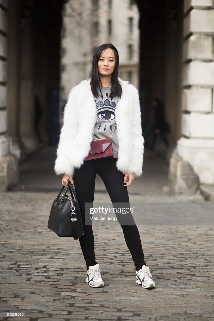 Model Li Xiao Xing exits the Emilio De La Morena show in vintage fur jacket, Kenzo sweater, Acne jeans, Saint laurent purse (red), Givenchy bag (black), and Chanel trainers during London Fashion Week Fall/Winter 2015/16 at Somerset House on February 24, 2015 in London, England.