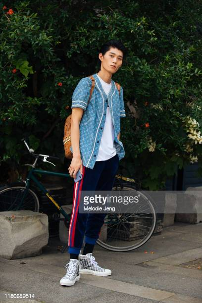 Model Licheng wears a blue Louis Vuitton Supreme top MCM backpack blue track pants and Dior logo white sneakers after the M1992 show during the Milan...