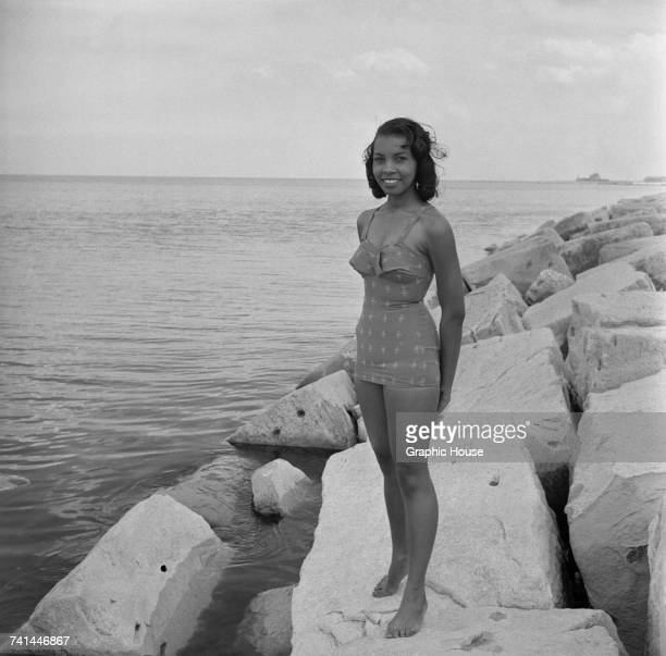 Model Lillie Jones wearing a onepiece swimsuit on the shore of Lake Michigan Chicago Illinois 1957