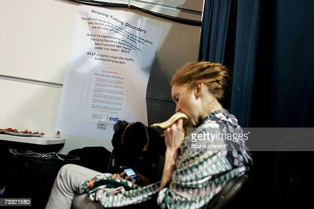 Model Lily Cole eats in front of a sign infroming models of eating disorders before Basso Brooke's Autumn/winter show at London Fashion Week on...