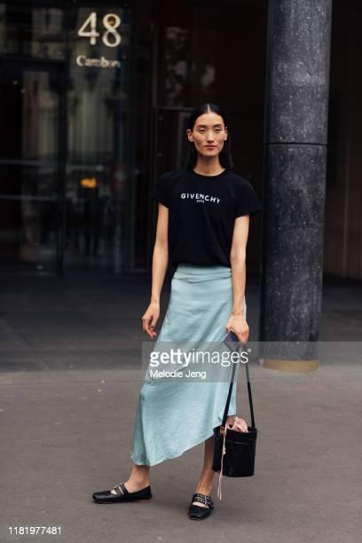 Model Lina Zhang wears a black Givenchy Paris shirt, teal asymmetrical silk skirt, black Givenchy bucket bag, and black Miu Miu ballerina flats after...