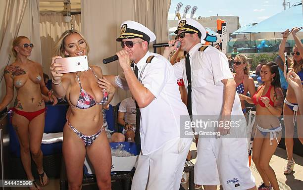 Model Lindsey Pelas records rappers Danny Boy and Jimbo of HardNox during their performance at the Sapphire Pool Day Club on July 3 2016 in Las Vegas...