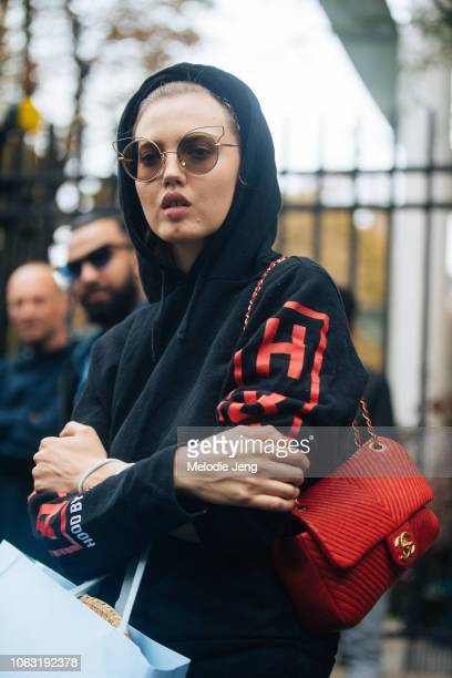 Model Lindsey Wixson wears cat wire frame sunglasses a black Hood By Air hoodie red Chanel bag after the Miu Miu show during Paris Fashion Week...