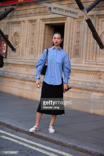 Model Ling Chen wears Airpods, a blue blouse, black skirt, and light pink jelly sandals after the Emilia Wickstead show during London Fashion Week...