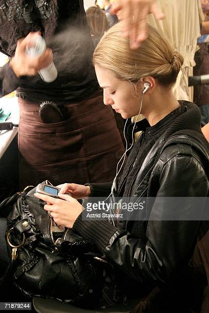A model listens to an MP3 player backstage at the Ports 1961 By Tia Cibani Spring 2007 fashion show during Olympus Fashion Week at the Atelier in...