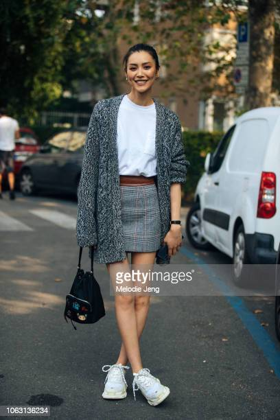 Model Liu Wen wears a gray cardigan white top gray patterned skirt black bag and white Balenciaga sneakers during Milan Fashion Week Spring/Summer...
