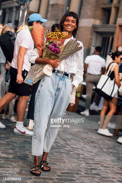 Model Liya Kebede wears a white lace top, blue jeans, black sandals, and holds two bouquets of flowers after the Tory Burch show and party on...
