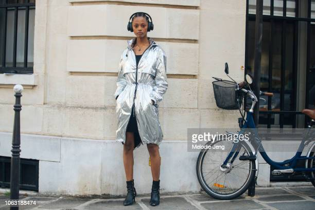 Model Londone Myers wears black headphones silver reflective Paco Rabanne jacket and black booties outside the Altuzarra show during Paris Fashion...