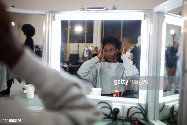 Model looks at her hair backstage prior to the Junko Shimada Spring-Summer 2019 Ready-to-Wear collection fashion show in Paris, on October 2, 2018.