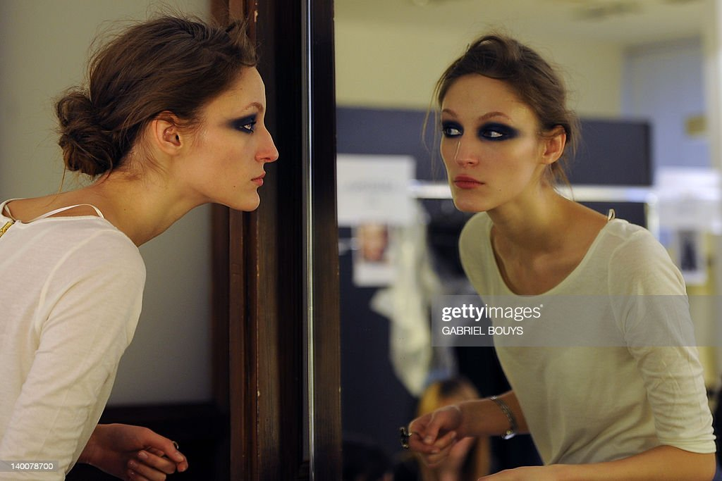 A model looks at her make-up in a mirror : News Photo