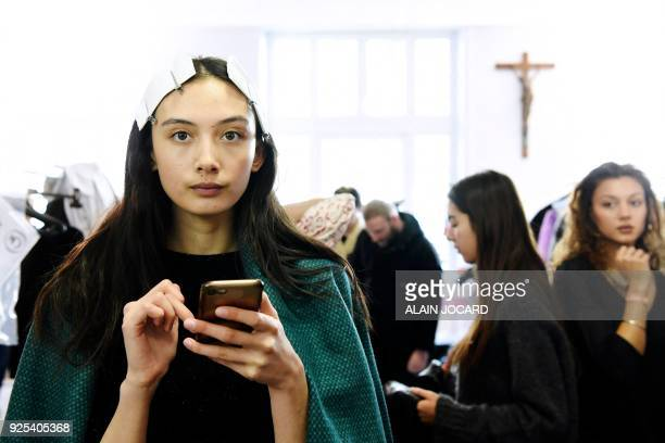A model looks at her phone as she gets ready in the backstage prior to the Aalto's 2018/2019 fall/winter collection fashion show on February 28 2018...