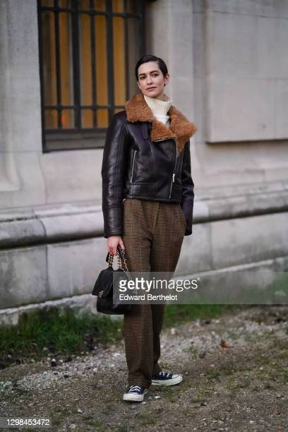 Model Louise de Chevigny wears a white wool turtleneck pullover, a brown leather aviator winter jacket with fluffy inner lining, brown suit pants...