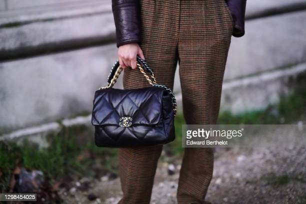 Model Louise de Chevigny wears brown suit pants with printed houndstooth patterns, a black leather quilted Chanel bag, outside the Grand Palais,...