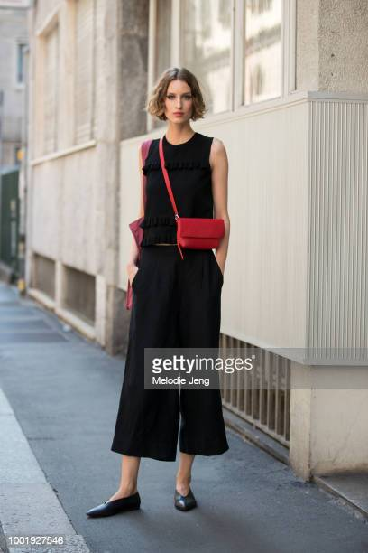 Model Luca Adamik wears a black sleeveless top, black culotte pants, black flats, and a small red cross-body bag after the Daks show during Milan...
