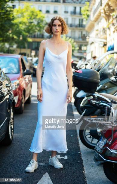 Model Luca Adamik wears a white silk dress and white sneakers after the Jean Paul Gaultier show during Couture Fashion Week Fall/Winter 2019 on July...