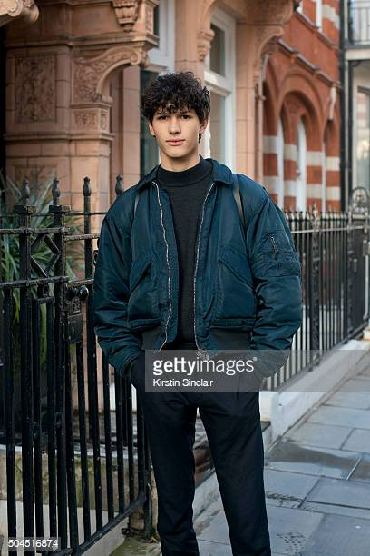 Model Lucas Santoni wears a vintage Schott bomber jacket Cos jumper and Rains bag on day 3 of London Collections Men on Januay 10 2016 in London...