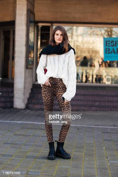 Model Lucia Lopez wears a white knit sweater, leopard print pants, and black boots after Roland Mouret during London Fashion Week February 2019 on...
