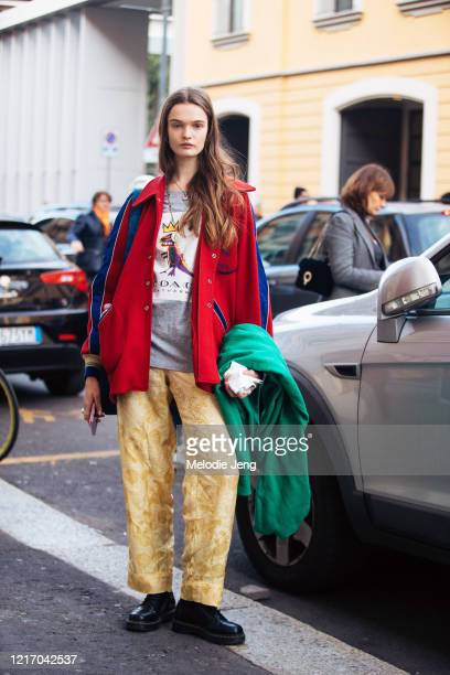 Model Lulu Tenney wears a red varsity-style jacket, gray Coach t-shirt, yellow silk print pants, and black boots after the Tod's show during Milan...