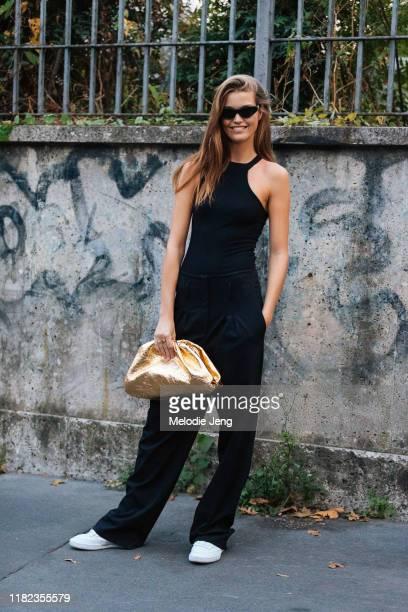 Model Luna Bijl wears a black tanktop, black pants, white sneakers, and gold Bottega Veneta pouch bag outside the Bottega Veneta show during Milan...