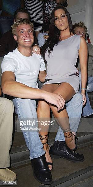 Model Lyndsey Dawn McKenzie sits on the lap of an unidentifed man at The Mr Universe competition at The Sway Club July 30 2003 in London