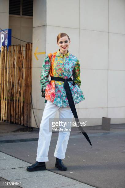 Model Lynn Palm wears a colorful floral brocade top with a black ribbon white pants and black boots after the Dries van Noten show during Paris...