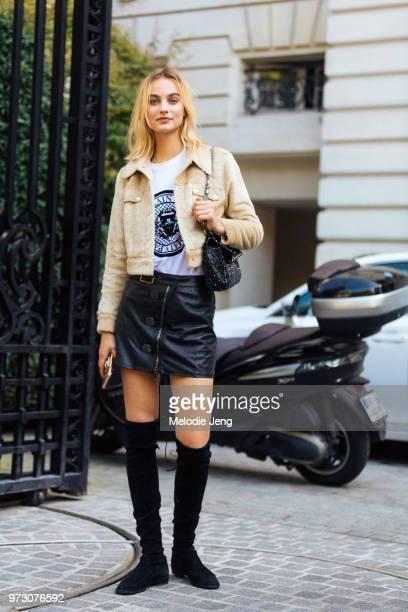 Model Maartje Verhoef wears a cropped tan jacket Balmain tshirt blue skirt black purse and black kneehigh boots during Paris Fashion Week...