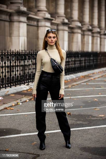 Model Madison Headrick wearing a cream sweater black leather pants and black fanny pack is seen outside the Redemption show during Paris Fashion Week...