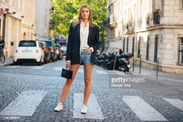 Model Madison Headrick wears a black blazer, white blouse, jean shorts, black square box, and white sneakers after the Zuhair Murad show during...
