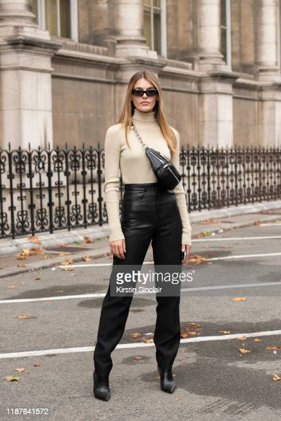 Model Madison Headrick wears a Sally LaPointe jumper Celine trousers Alexander Wang bag Givenchy boots on September 26 2019 in Paris France