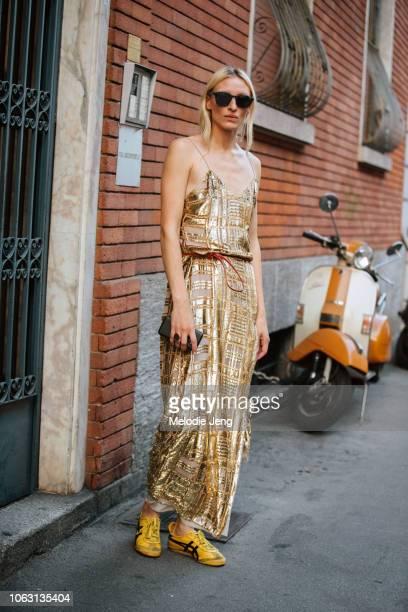 Model Maggie Maurer wears a gold Baja East dress and yellow Asics sneakers during Milan Fashion Week Spring/Summer 2019 on September 19 2018 in Milan...
