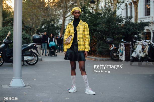 Model Mahany Per wearsa matching Guess yellow plaid beret and jacket, black skirt, high socks, and Nike Air Force 1s with colorful shoelaces after...