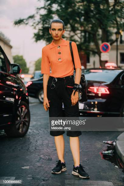 Model Maisie Dunlop wears an orange Ellery polo oversize button top black capri pants and black Nike sneakers after Valentino during Couture...