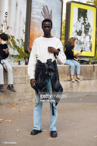 Model Malick Bodian wears a white knit sweater, black leather jacket around his waist, blue jeans, and black boots after the Haider Ackermann show...