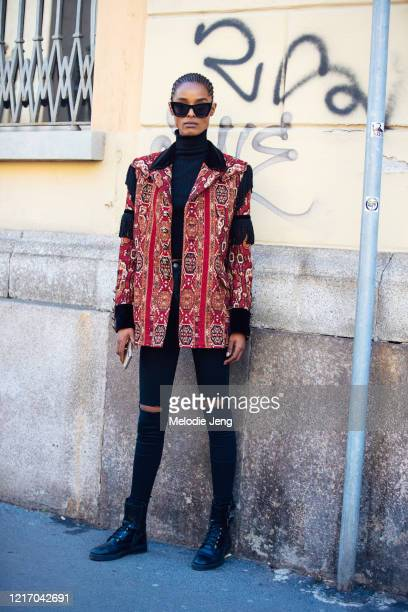 Model Malika Louback wears black sunglasses, a red Etro Paisley print jacket, black skinny jeans, and black booties after the Etro show during Milan...