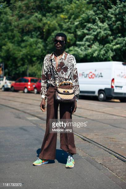 Model Mamadou Lo wears a blue floral shirt, brown pants, brown Gucci bag, and green Nike x Sacai sneakers after the Fendi show during the Milan Men's...