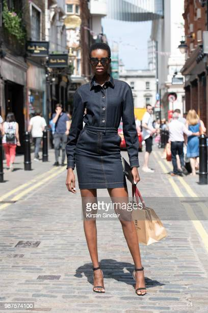 Model Maria Borges wears a Denim dress and strappy heels during London Fashion Week Men's on June 10 2018 in London England